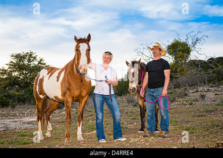 Mature couple with horses, Male 50 Caucasian, Female 45 Caucasian, Texas, USA Stock Photo