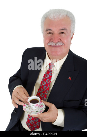 Turkish business man drinking his coffee, wearing red tie and suit. Isolated on white. - Stock Photo