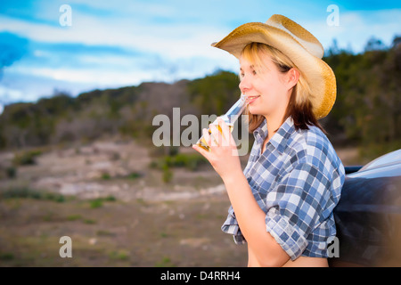 Portrait of country girl holding bottle of beer, Female 19 Caucasian, Texas, USA - Stock Photo