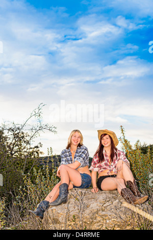 Friends - Two female teenagers in country girl attire sitting on a rock, Females 19 Caucasion, Texas, USA - Stock Photo