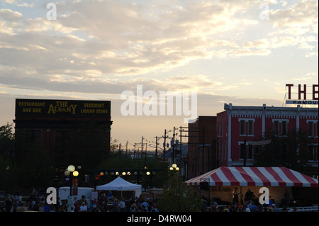 Twilight sunset view The Wrangler and Albany Liquor Mart rising above music tents and people, Cheyenne Depot Plaza, - Stock Photo