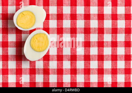two halves of a boiled egg on checkered tablecloth - Stock Photo