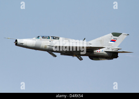 A Serbian Air Force MiG-21UM jet fighter with air brakes, in flight over Serbia. - Stock Photo