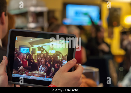 NY Mayor Michael Bloomberg, left, seen on an iPad, speaks at a press conference - Stock Photo