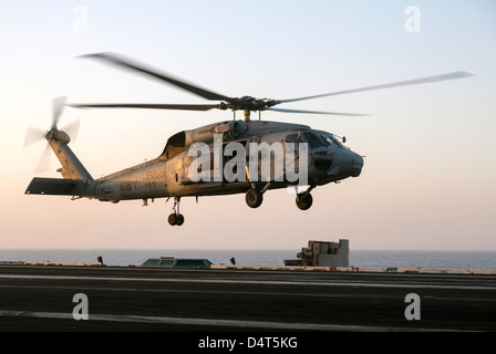 A Sikorsky SH-60F Seahawk lands on the flight deck of USS Dwight D. Eisenhower - Stock Photo