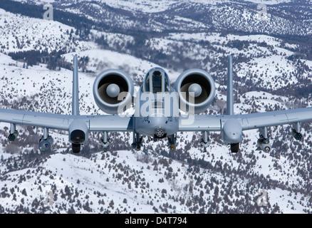 An A-10C Thunderbolt flies over the snowy Idaho countryside. - Stock Photo