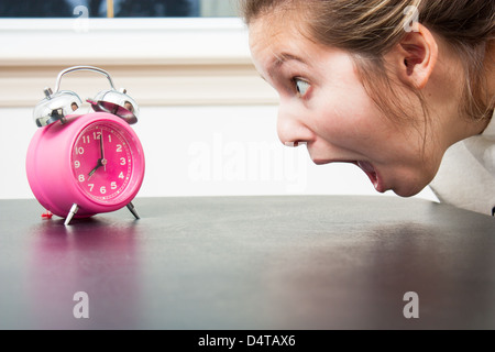 Close up as a young woman gapes at a pink alarm clock in shocked panic - Stock Photo