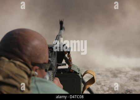 U.S. Contractor firing the automatic PKM 7.62 machine gun on the firing range in Kunduz, Afghanistan. - Stock Photo