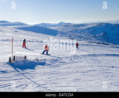 2 snowboarders and a skier on ski run, Cairngorm Mountain Ski Centre near Aviemore, beautiful sunny day, Cairngorms, - Stock Photo