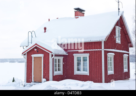 Traditional finnish wooden farm house covered in snow in winter - Stock Photo