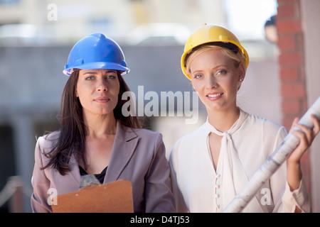 Businesswomen wearing hard hats - Stock Photo