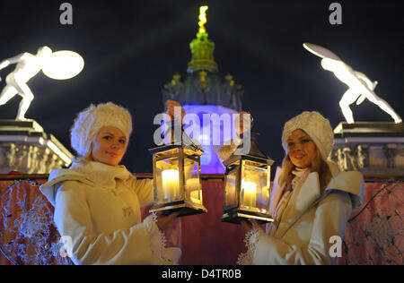 Two women dressed as angels hold lanterns while posing for photographers in front of Charlottenburg Castle and the - Stock Photo