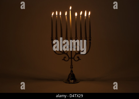 Menorah with lit candles - Stock Photo