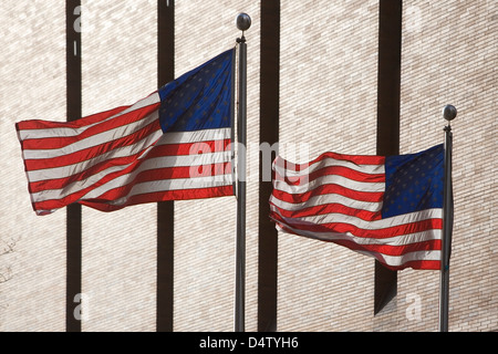 American flags flying by skyscraper - Stock Photo