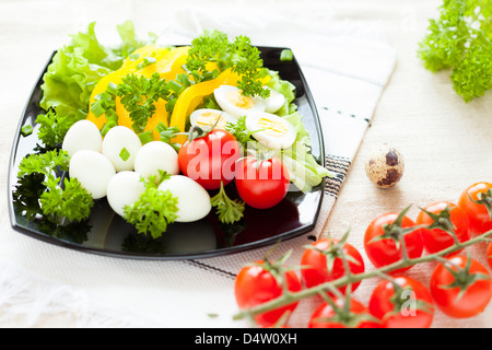 salad with fresh vegetables and quail eggs on a square plate, cherry tomato - Stock Photo