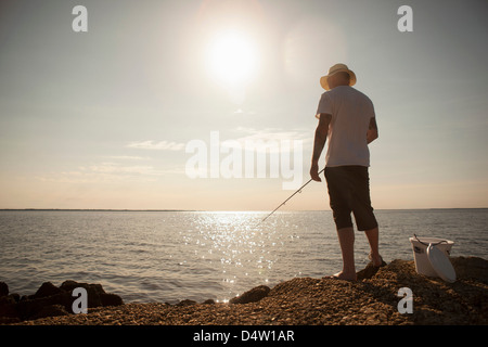 Man fishing in still ocean - Stock Photo