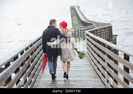 Couple walking on wooden dock - Stock Photo