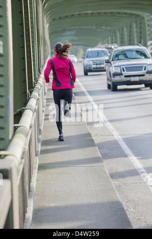 Woman running on urban bridge - Stock Photo
