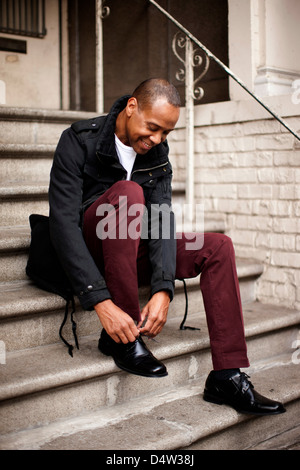 Man tying his shoes on front steps - Stock Photo