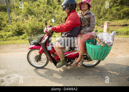 March 12, 2013 - Luang Prabang, Luang Prabang, Laos - A couple on a motorcycle heads north on Highway 13. The paving - Stock Photo