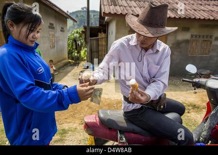 March 12, 2013 - Ban Phon Xieng, Luang Prabang, Laos - An ice cream vendor sells a couple of ice cream cones to - Stock Photo
