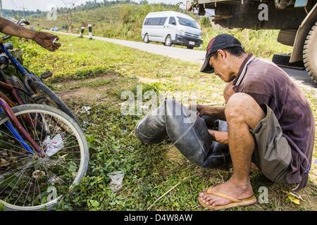 March 12, 2013 - Ban Phon Xieng, Luang Prabang, Laos - A man fixes a flat on truck along the side of Highway 13. - Stock Photo
