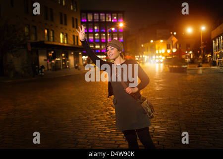 Woman hailing taxi on city street - Stock Photo