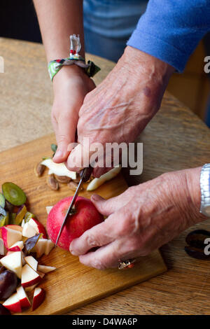 Senior Klara Fuerst (78) and student Sarah Boehm (20) cut fruit in their kitchen in Muenster, Germany, 14 September - Stock Photo