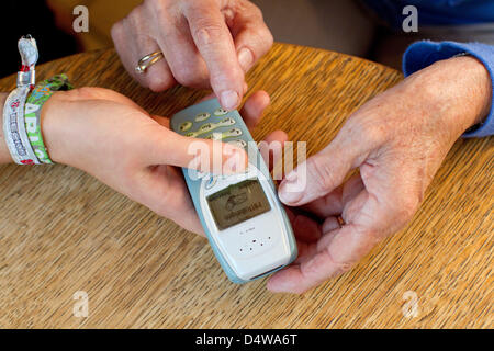 Senior Klara Fuerst (78) and student Sarah Boehm (20) use a mobile phone in their kitchen in Muenster, Germany, - Stock Photo