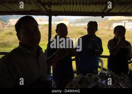 March 14, 2013 - Boten, Oudomxay, Laos - Three men and a woman (far right) sing karaoke in a restaurant/karaoke - Stock Photo