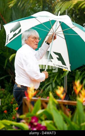 Formula One supremo Bernie Ecclestone walks beneath an umbrella during light rain at the Marina Bay Street Circuit - Stock Photo