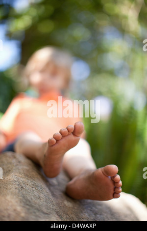 Close up of boy's feet on rock - Stock Photo