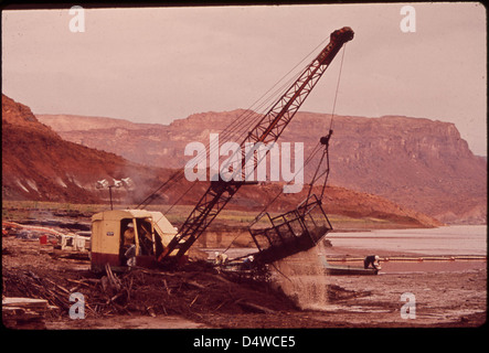 Dragline Shovel Scoops Up Oil - Laden Debris from Log Boom on San Juan River near Lake Powell, 10/1972 - Stock Photo