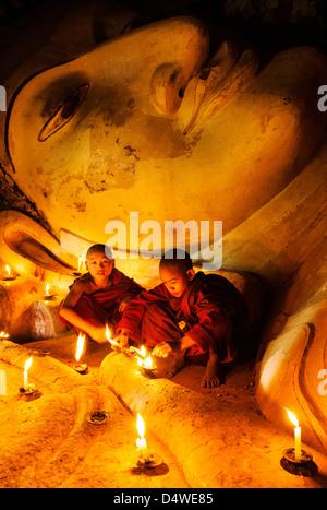 Buddhist monks praying in the temple to the reclining Buddha statue, Bagan, Burma (Myanmar) - Stock Photo