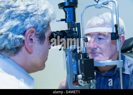 Doctor giving patient eye exam - Stock Photo
