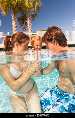Parents and toddler in swimming pool - Stock Photo