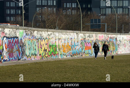 People go for a walk along a section of the Berlin Wall decorated with graffiti at the East Side Gallery in Berlin, - Stock Photo
