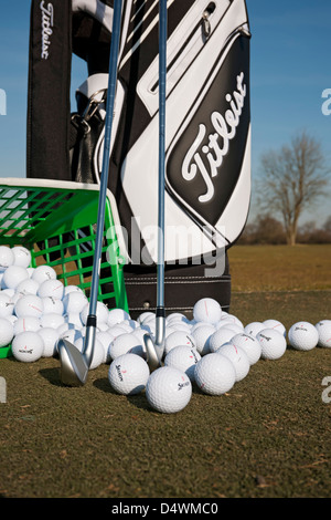 Titleist golf bag and clubs with range balls on a golf practice ground England UK United Kingdom GB Great Britain - Stock Photo