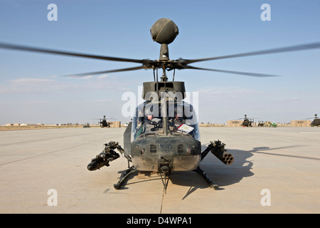 An OH-58D Kiowa helicopter prepares for liftoff from COB Speicher, Tikrit, Iraq, during Operation Iraqi Freedom. - Stock Photo