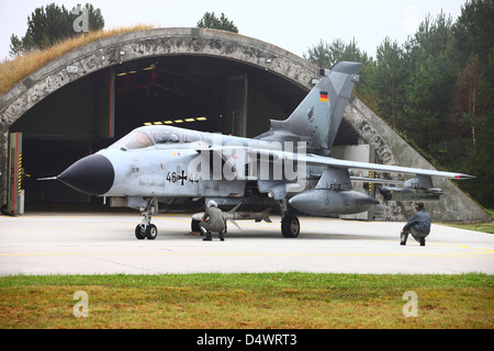 Ground crew conducting pre-flight-checks on a German Tornado ECR, armed with an HARM missile, in front of its shelter - Stock Photo