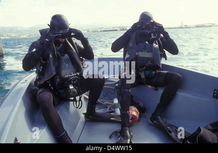 Navy SEALs combat swimmers in a utility boat adjust their dive masks. - Stock Photo