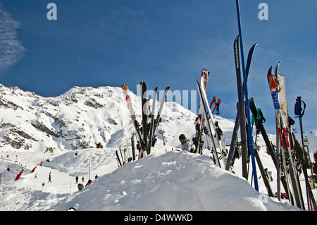 Skis standing in the snow, mountain background - Stock Photo
