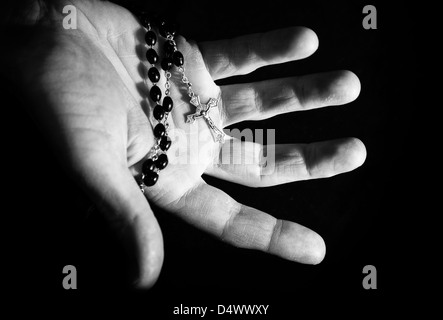 Helping hand holding onto rosary beads and cross. - Stock Photo