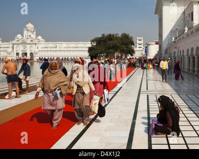 Pilgrims walking around the Holy Pool inside the Golden Temple complex Amritsar Punjab, India - Stock Photo