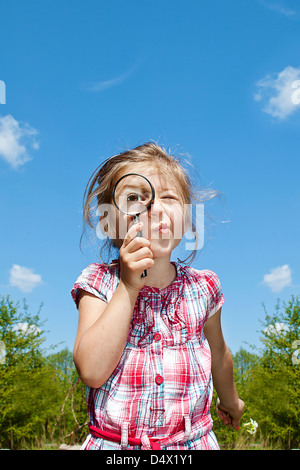little girl looking through magnifying glass - Stock Photo