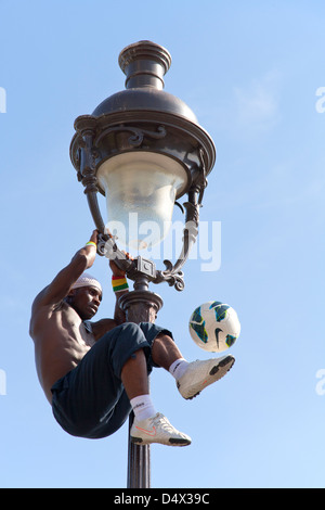 acrobatic performance artist at an old gas lamp on the hill of Sacre Coeur in Montmartre Paris - Stock Photo