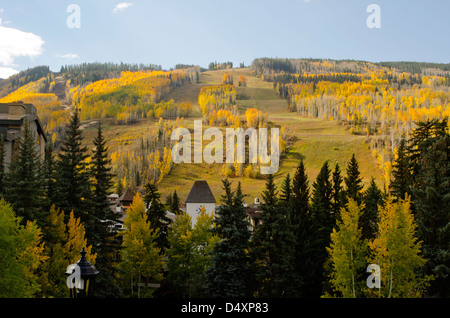 Vail Village and its iconic Clock Tower building set a stunning foreground to Autumn on the ski mountain behind. - Stock Photo