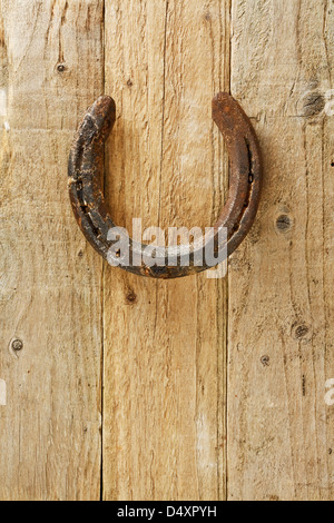 Old rustic horseshoe hanging on door said to bring good fortune and luck according to superstition - Stock Photo