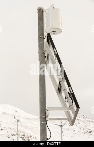 A small vertical axis wind turbine and solar panel on Kirkstone Pass, Lake District, UK. - Stock Photo