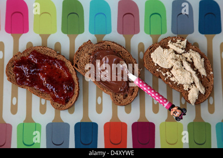 three home made sandwiches with chocolate spread, jam and Halva - Stock Photo